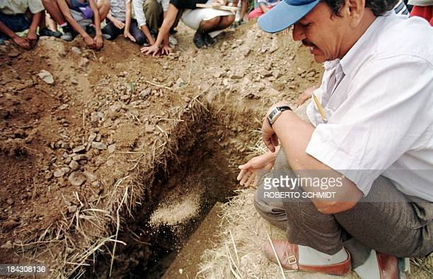 Pedro Lopez throws a handfull of dirt onto the casket of his 13-year-old daughter, Juanita, while saying some final words during the burial service...
