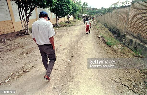 Pedro Lopez walks down a dirt street of a neighborhood of Tegucigalpa Honduras 17 November as he heads for a friend's house a few hours after burying...