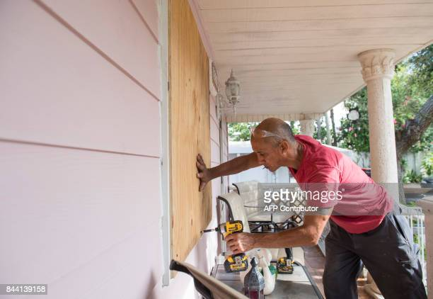 Pedro Marti covers the windows of his home with wood at the Sunnyside Trailer Park during preparations for Hurricane Irma in West Miami Florida...