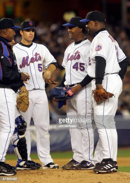 Pedro Martinez of the New York Mets smiles on the mound with teammates David Wright and Carlos Delgado and manager Willie Randolph before leaving the...