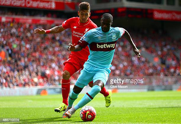 Pedro Mba Obiang of West Ham United and Roberto Firmino of Liverpool compete for the ball during the Barclays Premier League match between Liverpool...