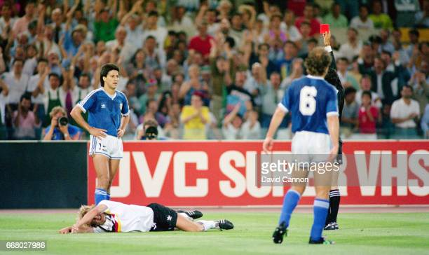 Pedro Monzon of Argentina is sent off with a straight red card by the referee Edgardo Codesal after fouling Jurgen Klinsmann of West Germany becoming...