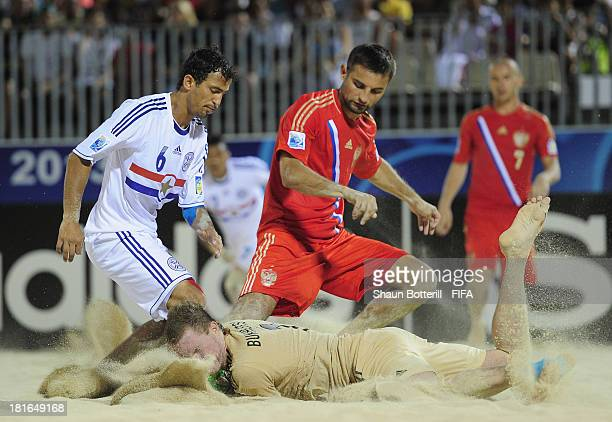 Pedro Moran of Paraguay is challenged by Alexey Makarov and Andrey Bukhlitskiy of Russia during the FIFA Beach Soccer World Cup Tahiti 2013 Group D...