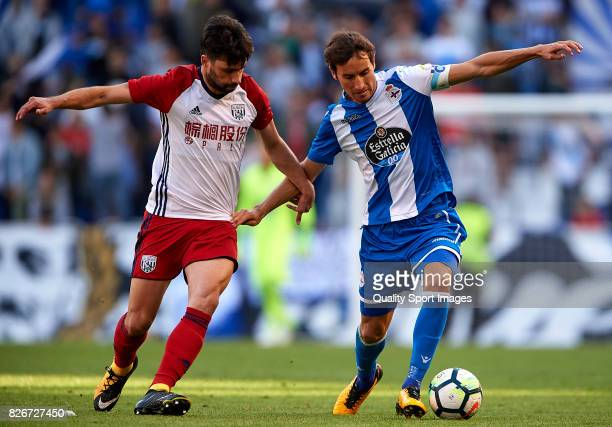 Pedro Mosquera of Deportivo de La Coruna is challenged by Claudio Yacob of West Bromwich Albion during the Pre Season Friendly match between...
