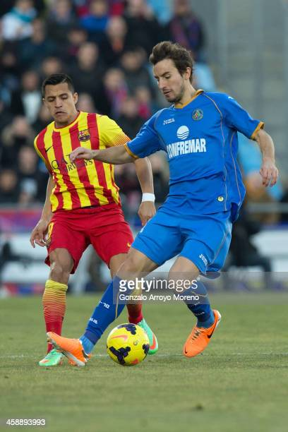 Pedro Mosquera of Getafe CF competes for the ball with Alexis Alejandro Sanchez of FC Barcelona during the La Liga match between Getafe CF and FC...