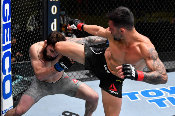 Pedro Munhoz of Brazil kicks Jimmie Rivera in a bantamweight bout during the UFC Fight Night event at UFC APEX on February 27, 2021 in Las Vegas,...