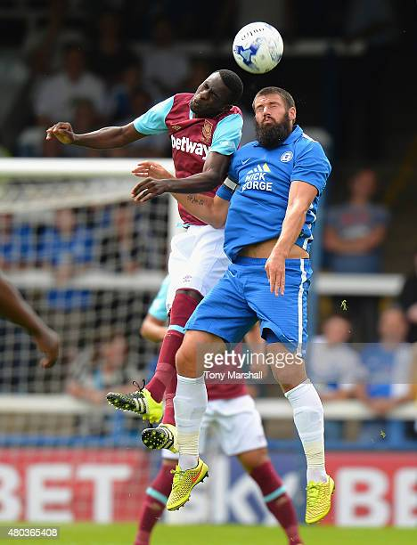 Pedro Obiang of West Ham United is tackled by Michael Bostwick of Peterborough United during the Pre Season Friendly match between Peterborough...
