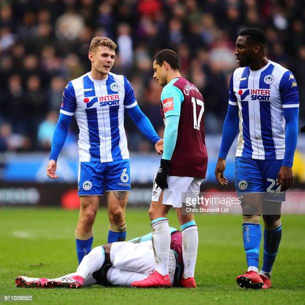 Pedro Obiang of West Ham United lies injured as Max Power of Wigan Athletic looks on during the Emirates FA Cup Fourth Round match between Wigan...