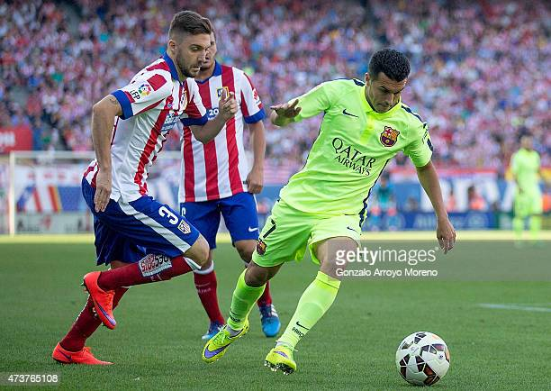 Pedro of Barcelona holds off Guilherme Siqueira of Atletico MadrArsene Wenger manager of Arsenal during the La Liga match between Club Atletico de...