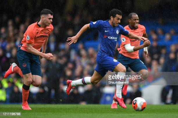 Pedro of Chelsea breaks away from Michael Keane and Djibril Sidibe of Everton to score his team's second goal during the Premier League match between...
