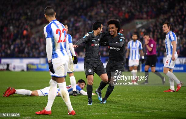 Pedro of Chelsea celebrates after scoring his sides third goal with Willian during the Premier League match between Huddersfield Town and Chelsea at...