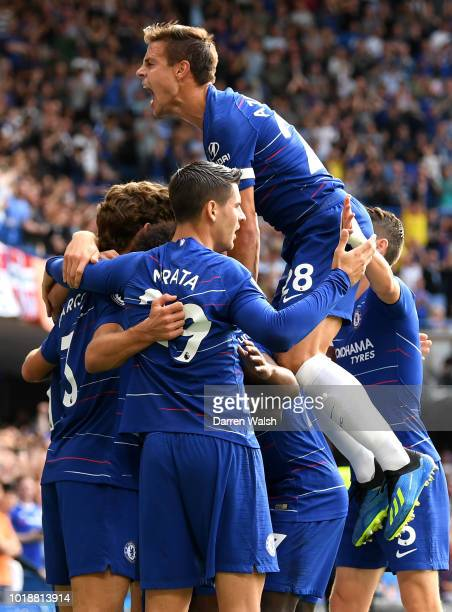 Pedro of Chelsea celebrates after scoring his team's first goal with team mates during the Premier League match between Chelsea FC and Arsenal FC at...