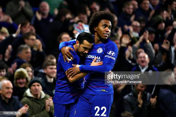 Pedro of Chelsea celebrates scoring his sides first goal with teammate Willian during the Premier League match between Chelsea FC and Newcastle...
