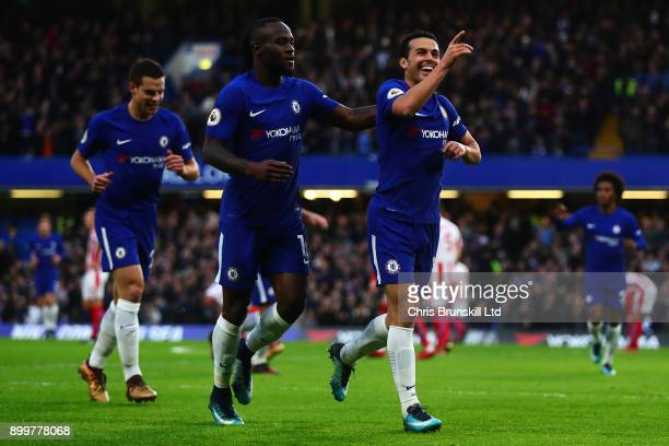Pedro of Chelsea celebrates scoring his side's third goal with teammate Victor Moses during the Premier League match between Chelsea and Stoke City...