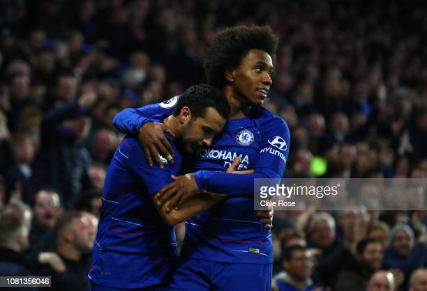 Pedro of Chelsea celebrates with teammate Willian after scoring his team's first goal during the Premier League match between Chelsea FC and...