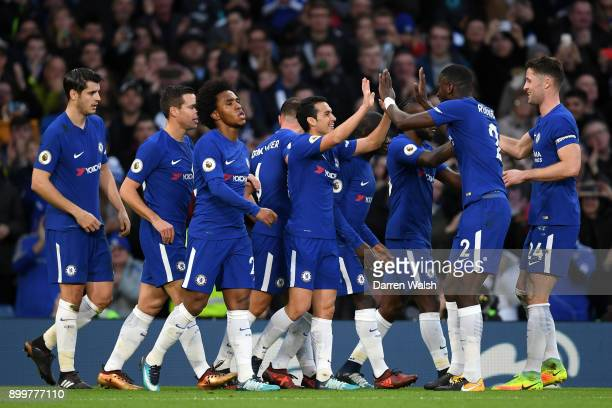 Pedro of Chelsea celebrates with teammates after scoring his sides third goal during the Premier League match between Chelsea and Stoke City at...