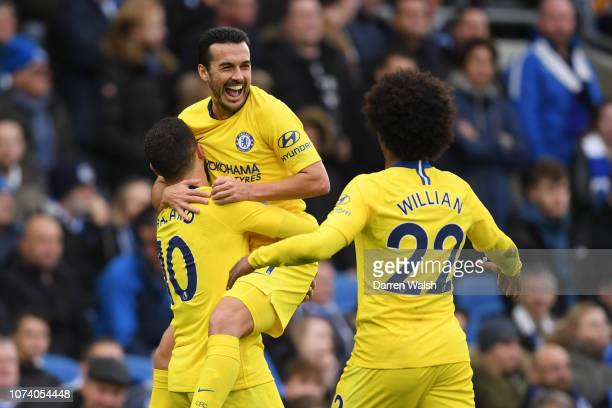 Pedro of Chelsea celebrates with teammates Eden Hazard and Willian after scoring his team's first goal during the Premier League match between...