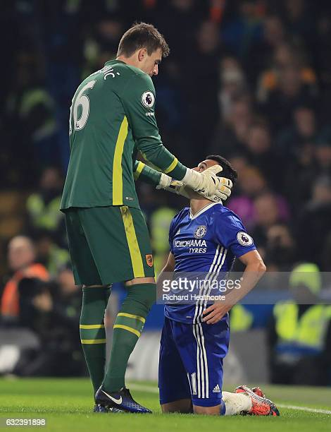 Pedro of Chelsea is consoled by Eldin Jakupovic of Hull City during the Premier League match between Chelsea and Hull City at Stamford Bridge on...