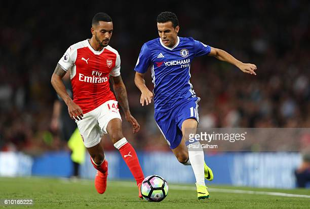 Pedro of Chelsea is put under pressure from Theo Walcott of Arsenal during the Premier League match between Arsenal and Chelsea at the Emirates...