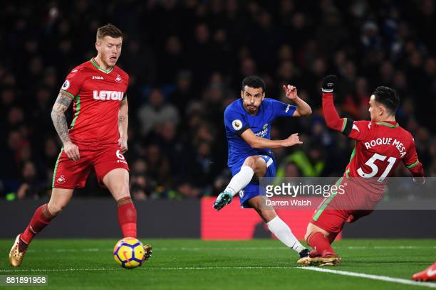 Pedro of Chelsea shoots as Roque Mesa of Swansea City attempts to block during the Premier League match between Chelsea and Swansea City at Stamford...