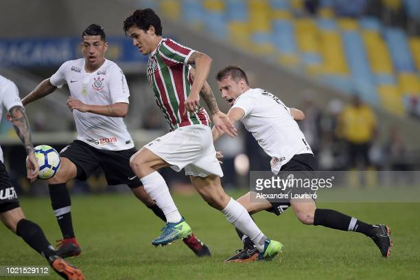 Pedro of Fluminense struggles for the ball with Ralf and Henrique of Corinthians during the match between Fluminense and Corinthians as part of...