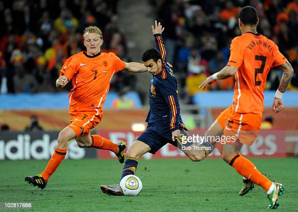 Pedro of Spain shoots between Dirk Kuyt and Gregory Van Der Wiel of the Netherlands during the 2010 FIFA World Cup Final between the Netherlands and...