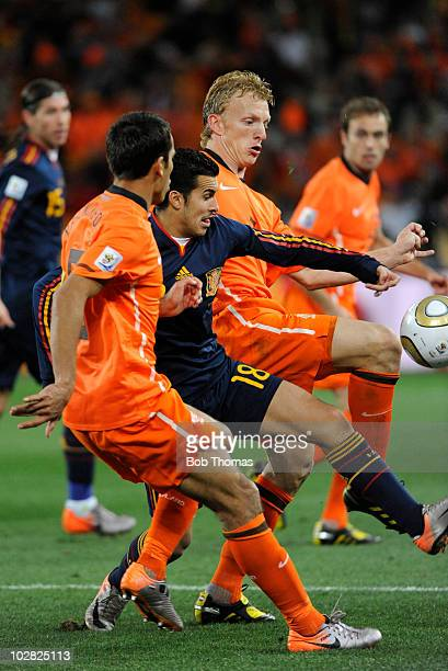 Pedro of Spain surrounded by Giovanni Van Bronckhorst and Dirk Kuyt of the Netherlands during the 2010 FIFA World Cup Final between the Netherlands...