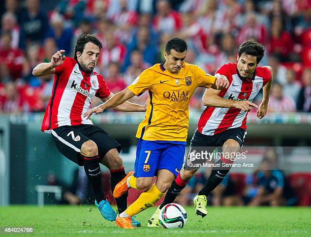 Pedro Rodriguez of FC Barcelona duels for the ball with Benat Etxebarria of Athletic Club during the Super Cup first leg match between of Athletic...