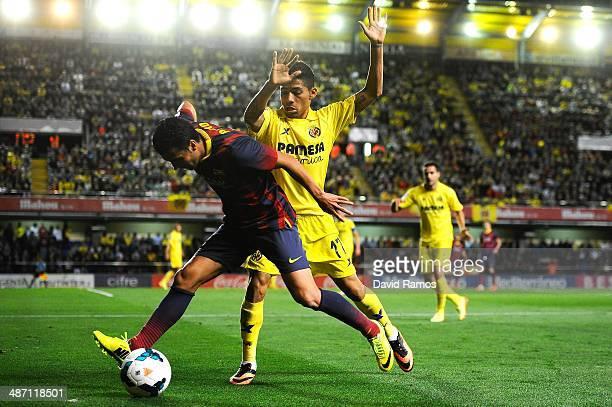 Pedro Rodriguez of FC Barcelona duels for the ball with Javier Aquino of Villarreal CF during the La Liga match between Villarreal CF and FC...