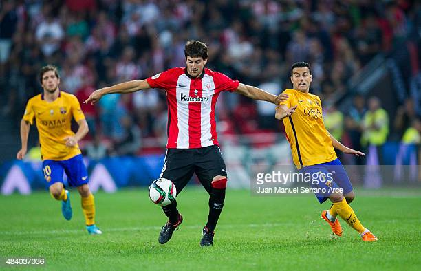 Pedro Rodriguez of FC Barcelona duels for the ball withÊMikel San Jose of Athletic Club during the Super Cup first leg match between of Athletic Club...