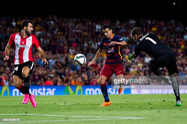 Pedro Rodriguez of FC Barcelona kicks the ball between Mikel Balenziaga and Gorka Iraizoz of Athletic Club during the Spanish Super Cup second leg...