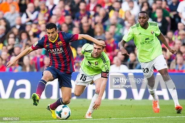 Pedro Rodriguez of FC Barcelona plays the ball alongside Oier Sanjurjo and Raoul Cedric Loe of CA Osasuna during the La Liga match between FC...