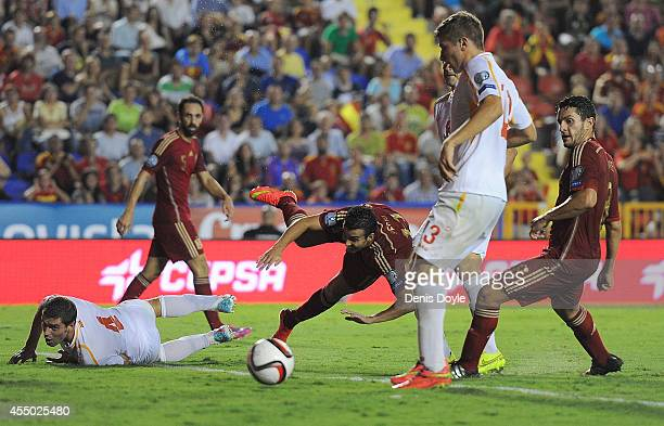 Pedro Rodriguez of Spain dives between Adrian Cuculi and Aleksander Damchevski of FYR of Macedonia during the UEFA EURO 2016 Group C Qualifier...