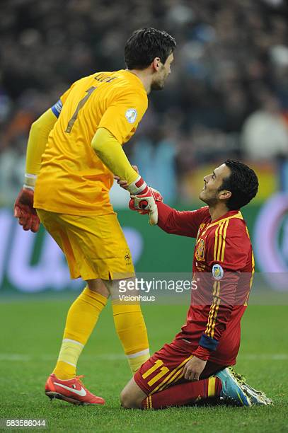 Pedro Rodriguez of Spain is helped to his feet by France goalkeeper Hugo Lloris during the Brazil 2014 FIFA World Cup Qualifying match between France...