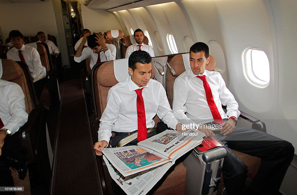 Pedro Rodriguez (L) of Spain reads a paper flanked by his teammate Sergio Busquets shortly after touch down at Johannesburg airport on June 11, 2010 in Johannesburg, South Africa.