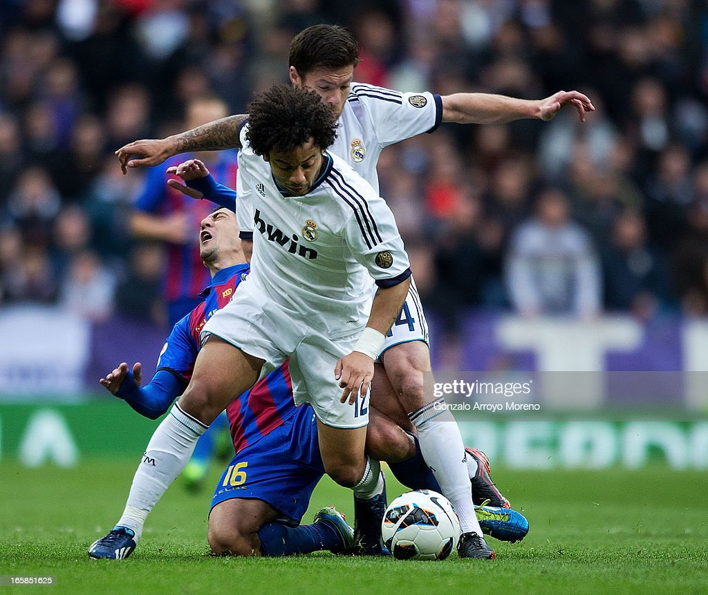 Pedro R'os of Levante UD (L) competes for the ball with Marcelo (2ndL) of Real Madrid CF and his teammate Xabi Alonso (R) complains during the La Liga match between Real Madrid CF and Levante UD at Santiago Bernabeu Stadium on April 6, 2013 in Madrid, Spain.