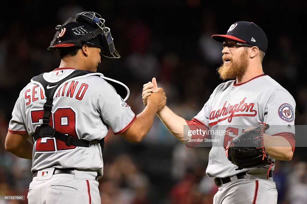 Pedro Severino #29 and Sean Doolittle #62 of the Washington Nationals celebrate after closing out the ninth inning of the MLB game against the Arizona Diamondbacks at Chase Field on May 11, 2018 in Phoenix, Arizona. The Washington Nationals won 3-1.