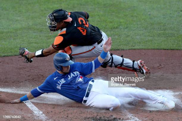 Pedro Severino of the Baltimore Orioles attempts to tag Joe Panik of the Toronto Blue Jays during the fifth inning at Sahlen Field on August 30, 2020...