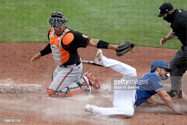 Pedro Severino of the Baltimore Orioles attempts to tag Randal Grichuk of the Toronto Blue Jays on a ball hit by Teoscar Hernandez of the Toronto...