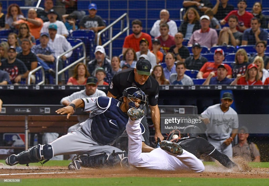 Pedro Severino #29 of the Washington Nationals tags out Cameron Maybin #1 of the Miami Marlins at homeplate in the eighth inning during the game between the Miami Marlins and the Washington Nationals at Marlins Park on May 26, 2018 in Miami, Florida.