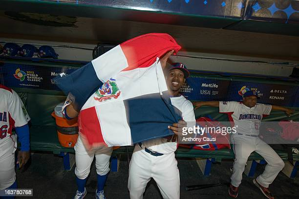 Pedro Strop of Team Dominican Republic waves the Dominican flag in the dugout before Pool C Game 1 between Dominican Republic and Venezuela in the...