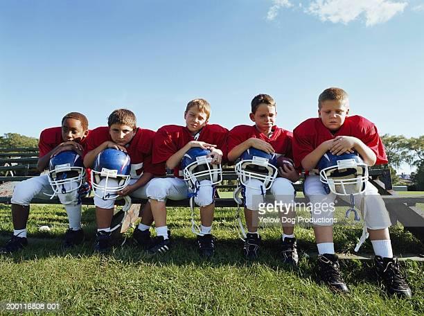 Pee wee football players (8-10) on sideline leaning on helmets