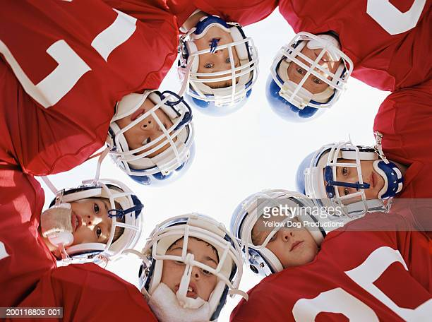 Pee wee football team (10-12) in huddle, portrait, low angle view