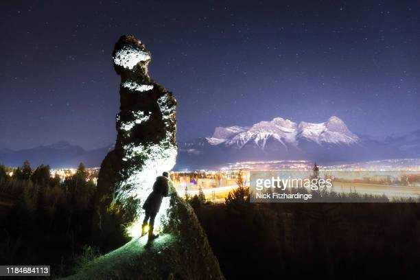 peeking at canmore from behind a hoodoo at night, canmore, alberta, canada - star wars stock pictures, royalty-free photos & images