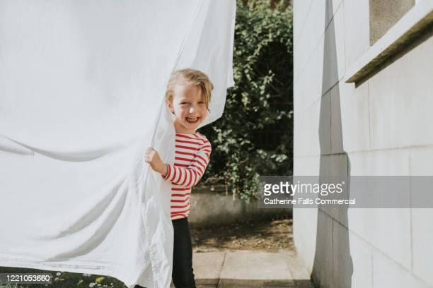 peeking out from behind washing - bettwäsche stock-fotos und bilder
