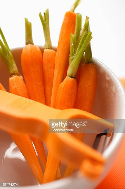 Peeled carrots in white cup with peeler