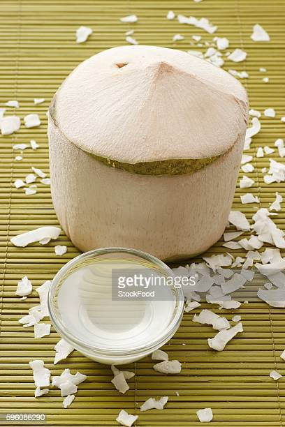 A peeled coconut, coconut water and coconut shavings on a bamboo mat
