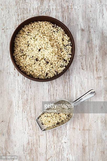 peeled hamp seeds, wooden bowl and spoon - hemp seed stock photos and pictures