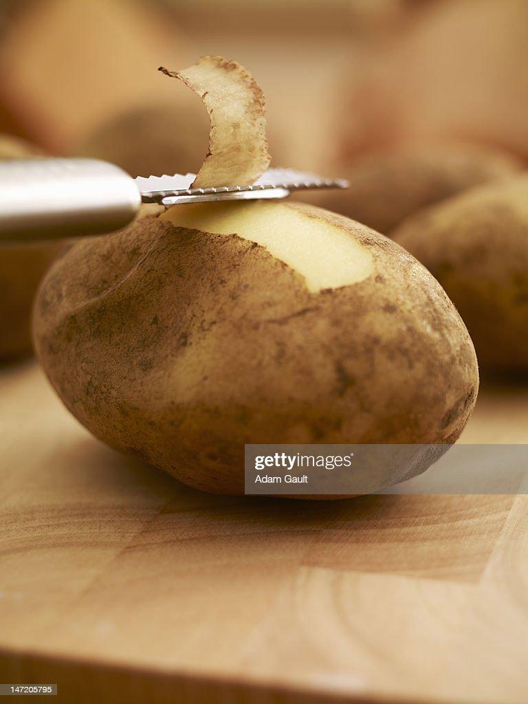 Peeler removing skin from potato : Foto de stock