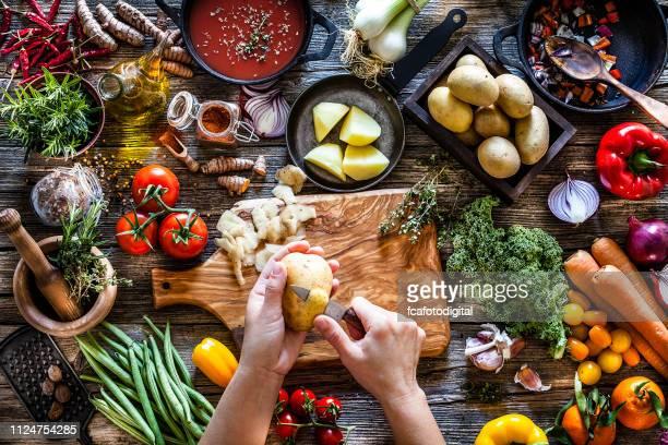 台所のテーブルの上にジャガイモを剥離 - 皮をむく ストックフォトと画像